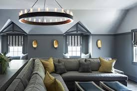 gorgeous gray family room boasts to gray washed desks positioned behind a gray pit sectional topped with gray and yellow pillows lit by a ralph lauren roark