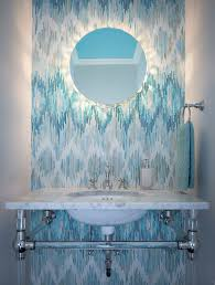fantastic powder room features floor to ceiling accent wall clad in new ravenna loom jewel glass mosaic tiled backsplash adorned with round frameless mirror