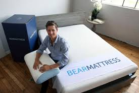 bed in a box mattress. In This Tuesday, Aug. 16, 2016, Photo, Scott Paladini, CEO Of Bear Mattress,  Sits With A Sample Newly-designed Pillow And Shipping Box In Bed Mattress O