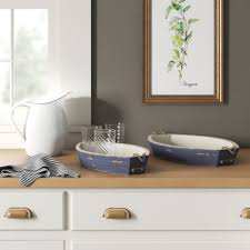 A tray is a foundational piece for your coffee table decor because it anchors the look, creates a zone, and is a super clever way of arranging small objects into an intentional grouping. Demby 2 Piece Coffee Table Tray Set Birch Lane