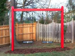 red black and white swing set in yard