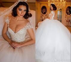 Designer Princess Ball Gown Wedding Dresses 2019 Luxury Lace Arabic Ball Gown Wedding Dresses Illusion V Neck Bodice Pearls Beaded Cap Sleeve Dubai Bridal Gowns Princess Puffy Designer Designer