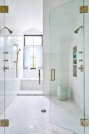 Stunning large seamless glass walk-in shower is clad in white marble mini  brick floor tiles framed by large white brick wall tiles fitted with a  tiled ...
