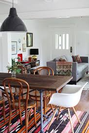 living room with a large wooden table and colourful rug with grey sofa in background