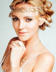 young blond woman dressed like ancient greek ess gold jewelry close up isolated golden