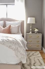 this bedroom executes the color pairing of pink and grey perfectly details of gold and silver through the side table drawer pulls and the table lamp