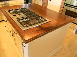 a natural solid walnut island with a classic edge and range cut out