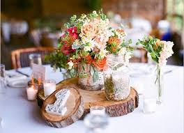 using wood slices and wood slabs as centerpieces is a fresh and innovative idea give a naturally rustic feel to your wedding with these slices
