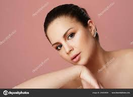 young with big brown eyes and dark eyebrows looking over empty beige colored studio background model with light make up