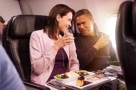 couple enjoying dinner and wine on air new zealand 777 200 premium economy class