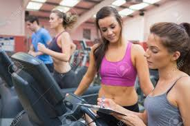 gym instructor female gym instructor and smiling woman in the gym on the treadmill