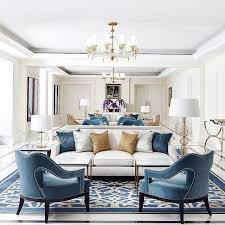 a predominantly white room with blue accent chairs a striking blue and white rug and gold accents