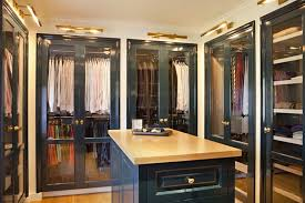 Gorgeous peacock blue walk-in closet with peacock blue glass-front closet  doors and peacock blue closet island with butcher block top.
