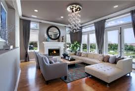 grey color family room with round wall mirror above fireplaces with small glass pendant lights