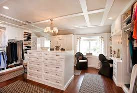 tall white closet island with recessed paneled drawers and combination shoe storage and hanging clothes rack