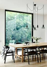 simple wood dining room chairs. simple wooden table, black dining chairs against a floor to ceiling window, providing natural light inside white interior scheme. wood room