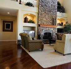 another luxurious living room dominated by large stone fireplace this room features dark hardwood flooring