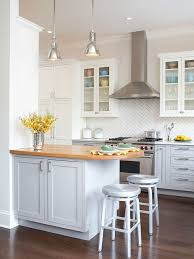 Elegant kitchen photo in Chicago with glass-front cabinets, white cabinets,  wood countertops