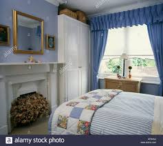 Patchwork quilt on bed in pale blue bedroom with white built in ...