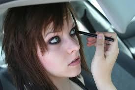 young woman doing her makeup