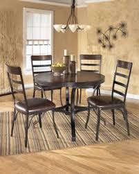 dorian by ashley the welded tubular metal frame covered in a dark bronze color finish supporting the rich rustic table tops makes the dorian dining