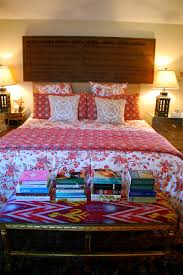 bohemian bedroom with bedside table and fl bedding also stacked books plus lamp shades and throw pillows also wall decor for eclectic bedroom design