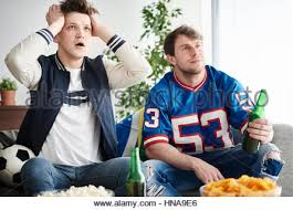 man watching soccer game on tv and drinking beer stock photo two young adults men watching soccer game stock photo