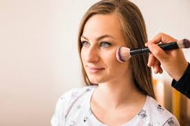 makeup artist applying blusher on woman s face free photo