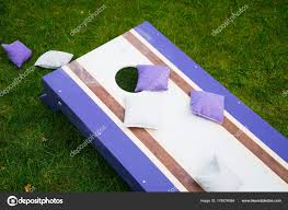 beanbag toss wood game board grass stock photo