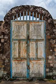 old rusty door with pad locks and rock arch at historical palace of the fon