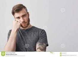 закройте вверх красивого кавказского человека с бородой и татуировки