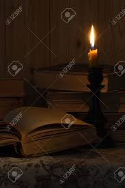 old book and a candle on the table stock photo 16038176