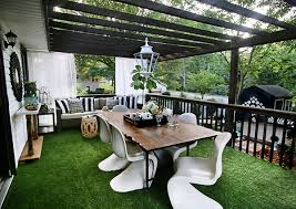 a beautiful deck decorated in black and white with lush artificial grass on the floor