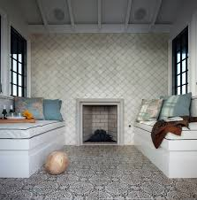 features built in window seat benches topped with white seat cushions with black piping facing each other atop a black and white moroccan tiled floor