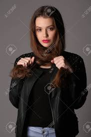 in a studded leather jacket holding her hair high fashion look perfect make up beautiful smiling isolated looking into the camera