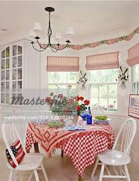 red white striped shades molding wallpaper border of swaged fabric and ivy candle wall sconces between windows chandelier red and white checked