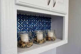 blue glass backsplash in tp cabinet with candles in jars