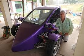 a man crouches next to a purple three wheeled car motorcycle