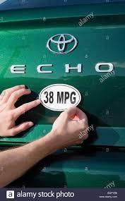 Man placing a 38 miles per gallon fuel efficiency bumper sticker ...