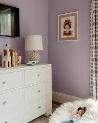 white and purple girls shared bedroom displays a tv over a dresser accessorize by books and a textured spheric desk lamp