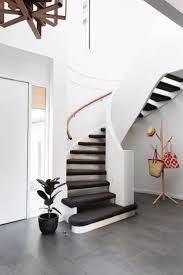 A white, spiral staircase adds drama to this eco-friendly redesign of a  Melbourne home, and incorporates carpeted treads for functionality.