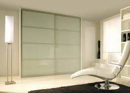 two piece of sliding frosted glass closet doors with silver metal frame added by high floor lamp and modern chair on white flooring