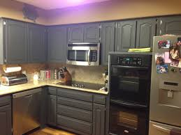 black color painting oak kitchen cabinet design with drawer and microwave shelf built in combined with light brown ceramic kitchen backsplash for small
