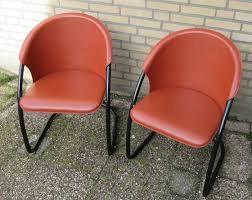 manufacturer unknown two italian black metal and red black leather dining chairs