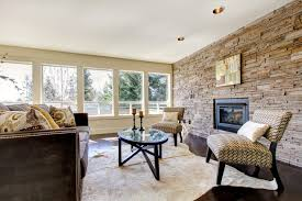 the natural stone wall in this living space makes it feel spa or resort like the furniture is comfortable and is upscale in its fabrics and finishes