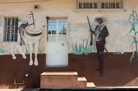 general pancho villa and his horse seven leagues painted on the side of a house in