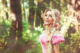 ツイスト三つ編みに長い髪を持つ美しい若い女性は森の中の散歩し