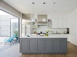 gray island with marble countertop white cabinets with side by side refrigerator light vinyl flooring ocean blue lazy chair 3 pendant lights marble