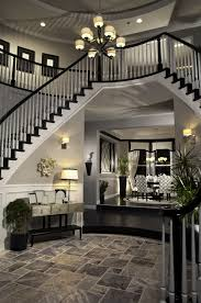 Double arched stairs descending down the round foyer creating a two-story  entrance way.