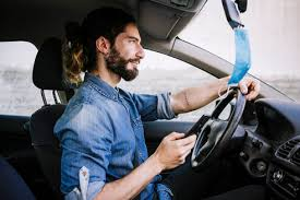 young man using hand sanitizer in car
